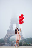 Parisian woman with red balloons in front of the Eiffel tower. Happy young woman in pink tutu dress with bunch of red balloons near the Eiffel tower in Paris Royalty Free Stock Photography