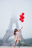 Parisian woman with red balloons in front of the Eiffel tower. Happy young woman in pink tutu dress with bunch of red balloons near the Eiffel tower in Paris Royalty Free Stock Photo