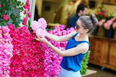 Parisian woman selecting peonies in flower shop Royalty Free Stock Images