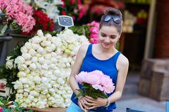 Parisian woman selecting peonies in flower shop Stock Images