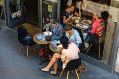 Parisians和游人享受食物和饮料在咖啡馆 免版税图库摄影
