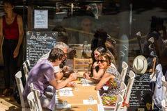 Parisians和游人享受食物和饮料在咖啡馆 免版税库存图片