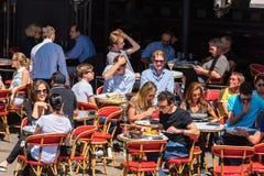 Parisians和游人享受食物和饮料在咖啡馆 免版税库存照片