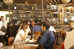 Parisians e os turistas passam a hora feliz em um café Imagem de Stock