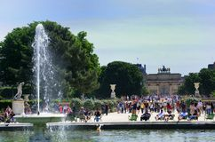 Parisians relaxing at Tuleries with fountain and lourve in background Royalty Free Stock Images