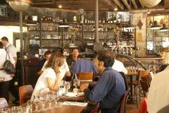 Parisians y los turistas pasan hora feliz en un café Imagen de archivo