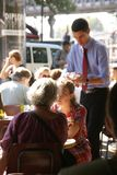 Parisians y los turistas pasan hora feliz en un café Fotografía de archivo libre de regalías