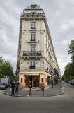 Parisien Hotel. PARIS, FRANCE, 20 MAY 2012 - A typical corner hotel in Paris built in traditional style with a couple in conversation standing outside the Royalty Free Stock Photos