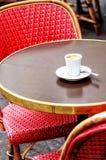 Parisisk kaféterrass med röda stolar och en espresso Royaltyfri Bild