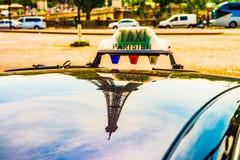 Parisiskt taxitak som visar Eiffeltorn som en reflexion arkivfoto