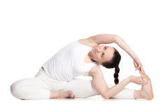 Parivrtta Janu Sirsasana. Sporty beautiful young woman in white sportswear sitting in Revolved Head to Knee pose, doing parivritta Janu Sirsasana, studio full royalty free stock photos
