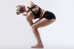 Parivrtta Utkatasana Pose. Sporty beautiful young woman practicing yoga, doing Revolved Chair Pose, Parivrtta Utkatasana, working out wearing black sportswear Stock Images