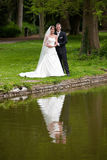 In the park. Bride and groom in the park near a pond reflecting Stock Image