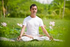 In the park. Young man sitting in lotus position outside in natural environment Royalty Free Stock Photo
