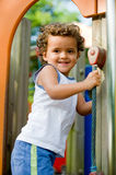 At The Park. A cute young kid playing on a climbing frame in a park Royalty Free Stock Images