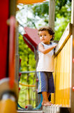 At The Park. A cute young kid playing on a climbing frame in a park royalty free stock photo