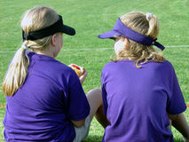 At the Park. Little girls watching softball game eating hotdog Royalty Free Stock Photo