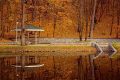 Park with arbour at fall autumn and lake reflection Stock Photo