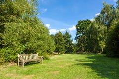 Park-Bank im schönen üppigen grünen Garten Stockfotos