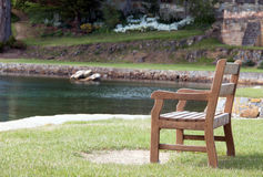 Park bench. Beautifully crafted timber park bench overlooking water Royalty Free Stock Photos