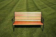 Park bench. Wrought iron and wood slat bench in a landscaped area with sun shining on the bench Stock Images