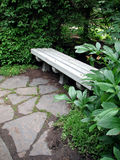 Park Bench. A stone bench sits to one side, just off a stone walkway, surrounded by greenery. A place to stop and rest during a leisure stroll through a park Royalty Free Stock Image