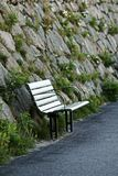 A lonely park bench placed by the wall. stock photography