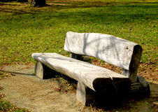 Park bench. A long, low park bench made of split logs Stock Photo