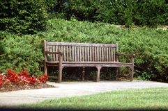 Park Bench. Empty Weathered Park Bench in garden with green grass and foliage Royalty Free Stock Photo