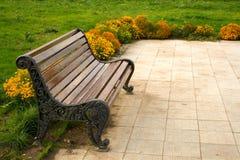 Park bench. Near yellow flowerbed Stock Photo