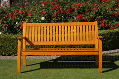 Park Bench. On a lawn with beautful red roses in the background Stock Image