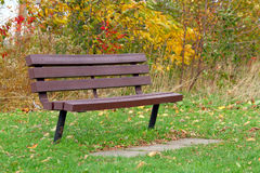 Park bench. Fall park view, a bench on a green grass and yellow leaves background. Shallow focus Royalty Free Stock Photography