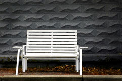 Park Bench. Isolated with gray brick background and leaves royalty free stock photography