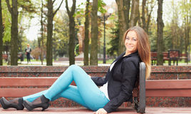 Park bench. Smiling girl in a black jacket on a park bench Royalty Free Stock Photo