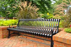 Park Bench. A park bench in a park setting for relaxing and leisure royalty free stock images