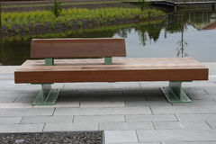 Park bench. A modern park bench, with river in the background royalty free stock photo