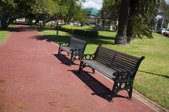 The Park Bench 3. 2 park benches in a garden with a footpath in the foreground Royalty Free Stock Image