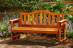 Park bench. Wooden bench in garden setting Royalty Free Stock Photos