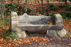 Park bench. Carved from log in autumn woods Royalty Free Stock Photos