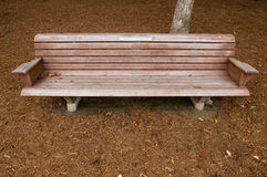 Park Bench. Single empty Park Bench and dried up ground in winter Royalty Free Stock Photography
