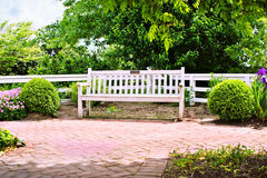 Park bench. White Park bench with white wooden fence and beautiful gardens Royalty Free Stock Photo