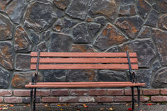 Park Bench against Stone Wall. An unoccupied park bench placed in front of a gray stone wall outside making a nice background scene stock images