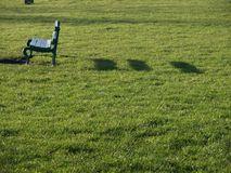 Park bench on an Autumn afternoon. Park bench and shadows Stock Image