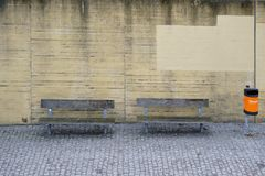 Park bench with bins. Park benches and an orange refuse bin stand on a striking concrete wall Stock Photo