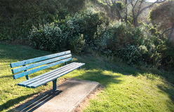Park bench. Blue park bench with misty morning sunlight and shadows in the background Stock Image