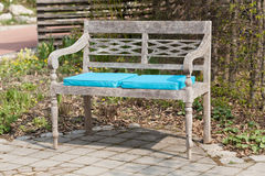 Park bench with blue seat cushions Royalty Free Stock Photo