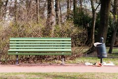Park-bench with congested garbage can. A green park-bench with a congested garbage can Royalty Free Stock Images