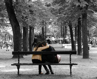 Park Bench Couple. Couple snuggling on a Park Bench in Paris, away from the crowd listening to the band Stock Photos