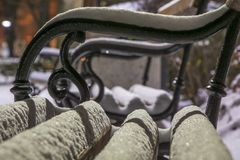 Park bench covered with snow. Winter background.Winter night and white snow Stock Photography
