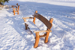 Park bench covered with snow on a winter day Stock Images